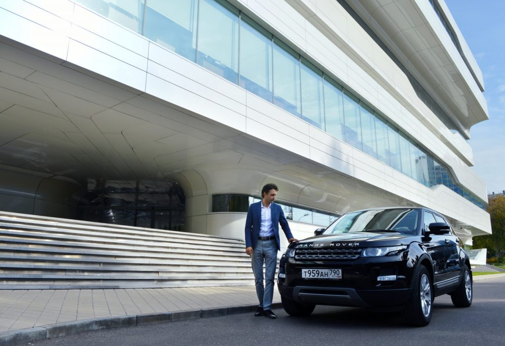 A well-dressed man outside of a fancy building with a black Range Rover.